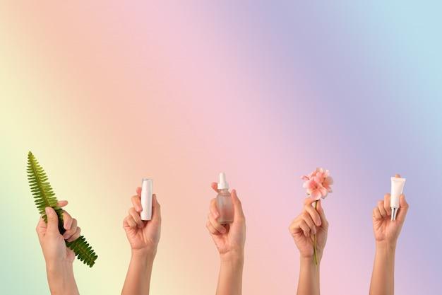 Cura della pelle cosmetica della tenuta della mano su fondo rosa.
