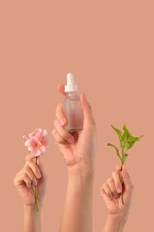 Cura della pelle cosmetica della tenuta della mano sulla parete rosa con la foglia ed il fiore. prodotto di bellezza naturale biologica.