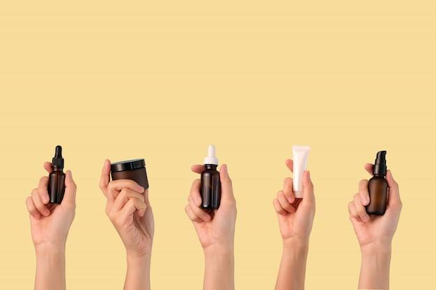 Cura della pelle cosmetica della tenuta della mano su fondo giallo.