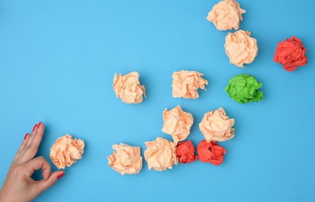 Tenere in mano fogli di carta colorata sgualciti su sfondo blu. concetto di soluzione, brainstorming, opposizione e confronto, mediatore nella risoluzione del problema