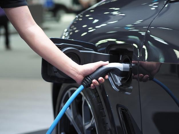 Tenere in mano la spina del veicolo di ricarica elettrica per ricaricare la batteria dell'energia pulita di colore nero dell'auto