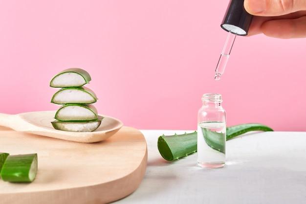 Tenere in mano l'estratto di gel di aloe vera biologico con piatto di legno e cucchiaio su uno sfondo rosa
