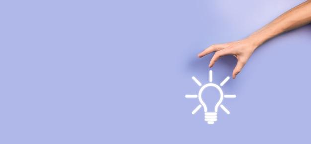 Tenere in mano la lampadina. tiene in mano un'icona luminosa di un'idea. con un posto per il testo. il concetto dell'idea imprenditoriale. concetti di innovazione, brainstorming, ispirazione e soluzione.