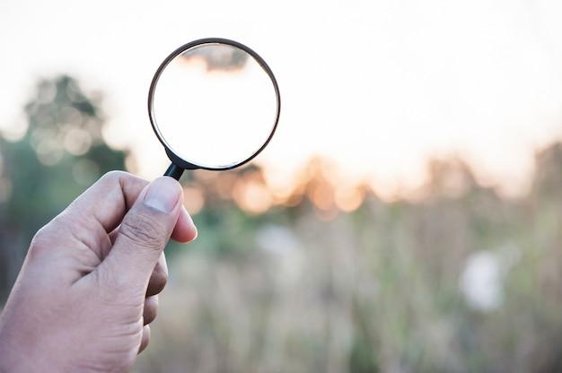Tenere in mano la lente di ingrandimento per la ricerca Foto Premium