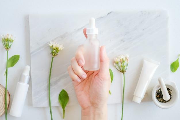 Mano tenere cura della pelle naturale sul tavolo di marmo con fiori, foglie e mortaio pestello.