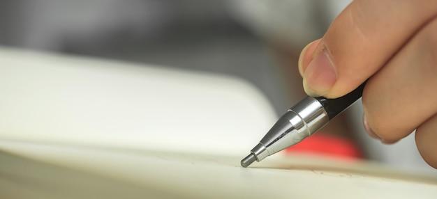 Tenere in mano le matite e disegnare o scrivere su un taccuino, foto di sfondo dell'insegna dell'hobby dell'artista con spazio di copia