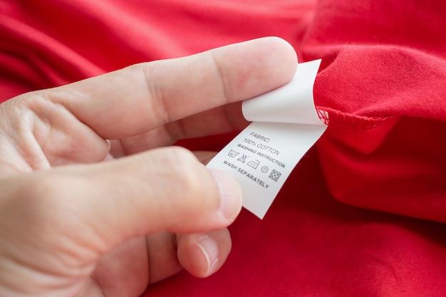 Tenere in mano e leggere al bucato bianco istruzioni per il lavaggio dell'etichetta dei vestiti su una camicia di cotone rossa