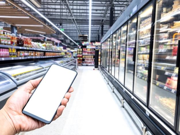 Tenere in mano lo schermo bianco dello smartphone sfocatura dello sfondo del centro commerciale