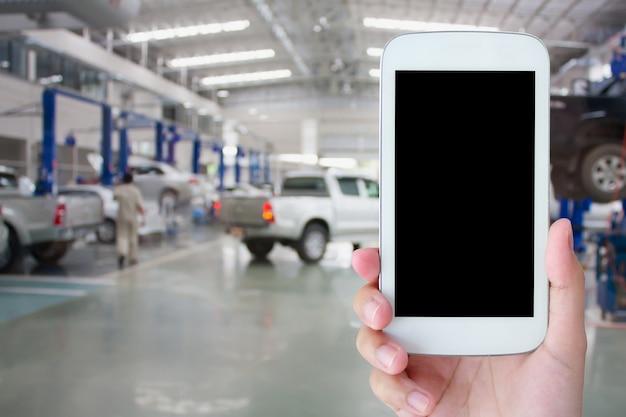 Tenere in mano lo smartphone con sfondo del centro di servizio di riparazione auto