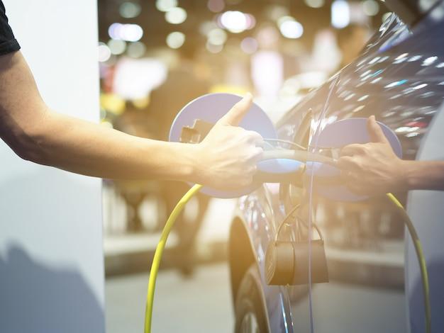 Tenere in mano e pollice in su la spina del veicolo di ricarica elettrica e il bagliore luminoso per ricaricare la batteria dell'auto