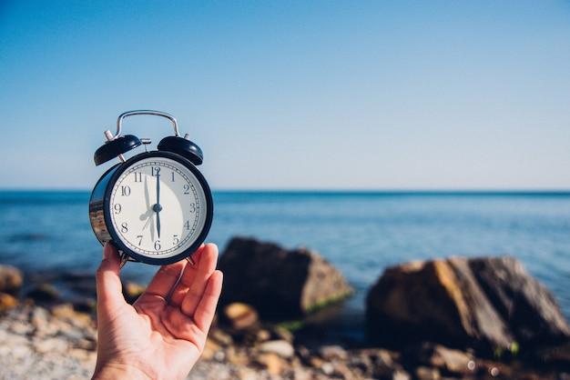 Tenere in mano l'orologio sullo sfondo della spiaggia. sveglia sul mare e la sabbia sullo sfondo in tempo diverso con le vacanze estive. concetto di tempo di vacanza.