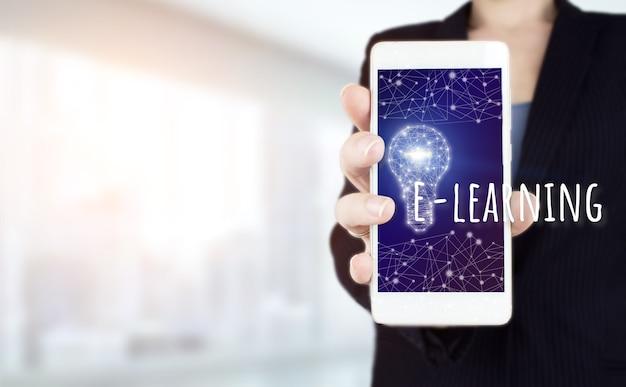 Tenere in mano lo smartphone bianco con la lampadina dell'ologramma digitale, segno di e-learning su sfondo sfocato chiaro. idea brillante di rete con lampadina. e-learning internet education webinar corsi online.