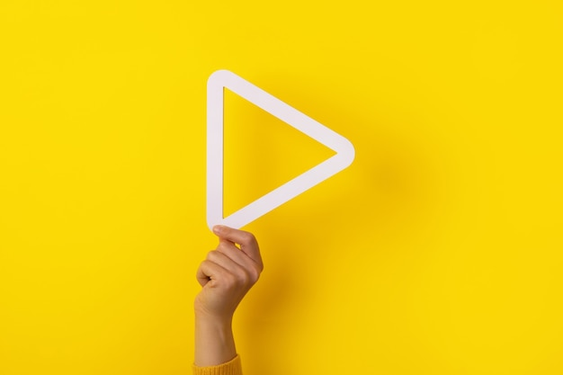 Mano che tiene il pulsante di riproduzione multimediale 3d su sfondo giallo