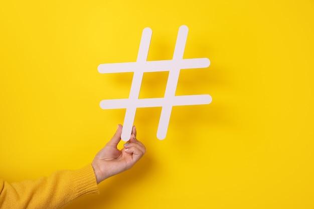 Mano che tiene un grande segno di cancelletto bianco, simbolo hashtag delle tendenze di internet e blog popolari, raccomandazione a seguire i contenuti dei social media.