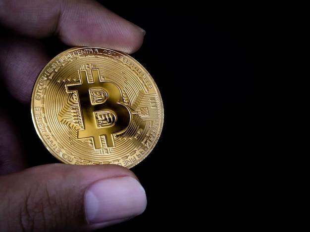 Mano che tiene bitcoin su sfondo nero