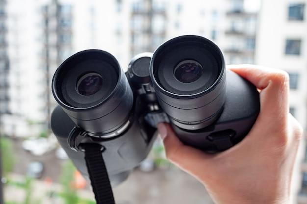 Mano che tiene il binocolo nero su uno sfondo sfocato di una finestra con vista della casa vicina per osservare i vicini, l'ambiente o la natura. messa a fuoco selettiva. vista del primo piano