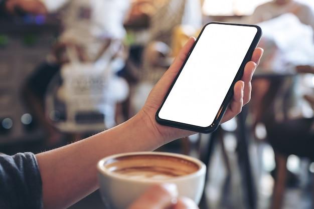 Una mano che tiene il telefono cellulare nero con schermo vuoto mentre beve il caffè nella caffetteria vintage