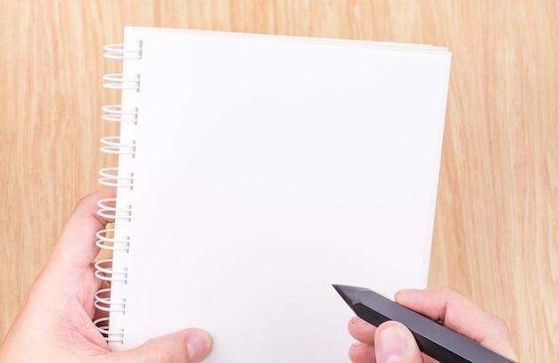 Passi la tenuta della matita nera e del libro aperto bianco vuoto sopra lo scrittorio di legno