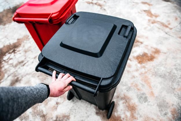 Mano che tiene il contenitore dei rifiuti nero.