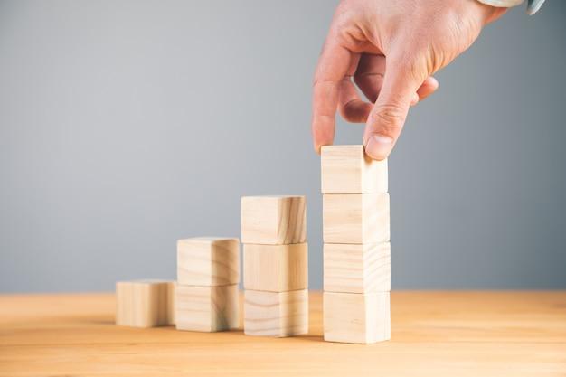 Mano che tiene i cubi di legno in bianco del blocco sul fondo della tavola, fondo di concetto di affari