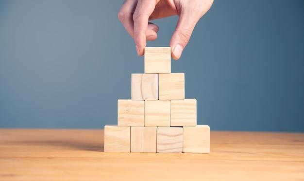 Mano che tiene i cubi di legno in bianco del blocco sul fondo della tavola, concetto di affari