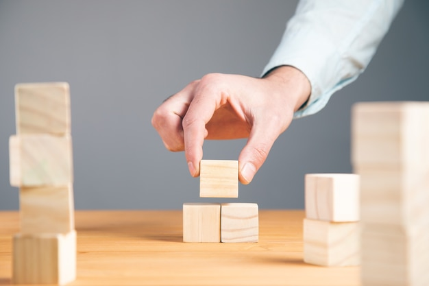 Mano che tiene i cubi di blocco di legno vuoti sul tavolo