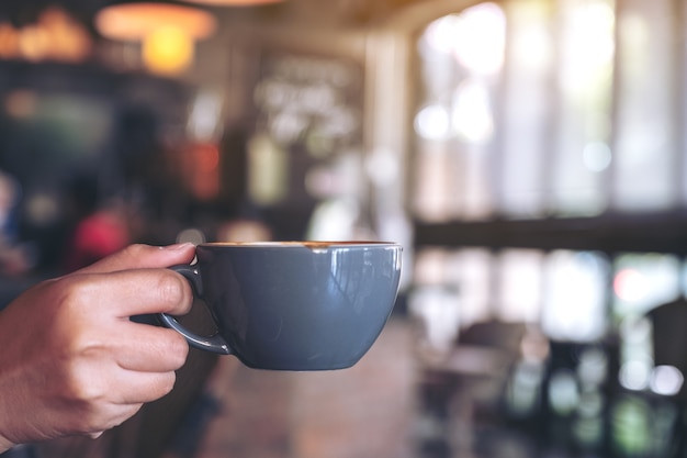 Mano che tiene una tazza blu di caffè caldo