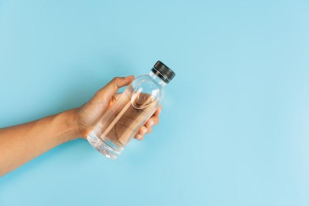 Bottiglia della tenuta della mano di acqua minerale sul blu
