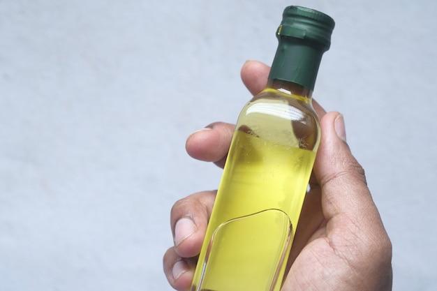 Mano che tiene una bottiglia di olio d'oliva