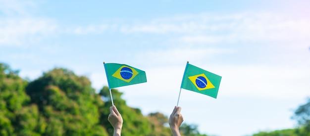 Mano che tiene la bandiera del brasile sul fondo del cielo blu. concetti di festa dell'indipendenza di settembre e felice celebrazione