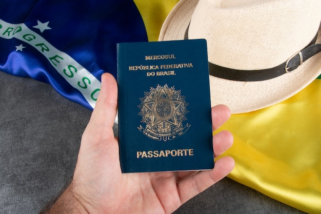 Mano che tiene il passaporto brasiliano con bandiera brasiliana