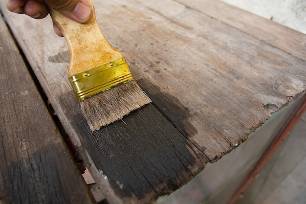 Mano che tiene una spazzola dipingere la superficie di tavole in legno con wood stain