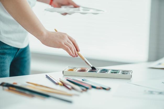 La mano che tiene un pennello con una vernice al tavolo