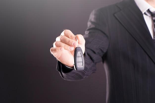 Una mano che tiene le chiavi della macchina e un telecomando per l'accesso senza chiavi key