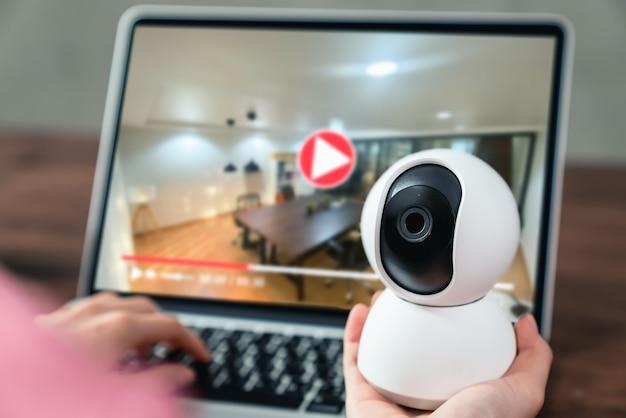 Mano che tiene la telecamera cctv e utilizzo di laptop con guardando la registrazione video, tecnologia di sorveglianza.