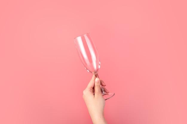 Mano che tiene un bicchiere di champagne su uno sfondo rosa