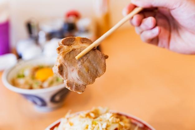 Una mano che regge chashu con le bacchette di tonkotsu chashu ramen.