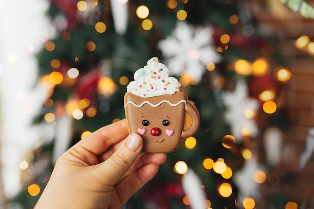 Mano che tiene il biscotto di pan di zenzero di natale e decorazioni all'albero di natale, tazza di pan di zenzero.