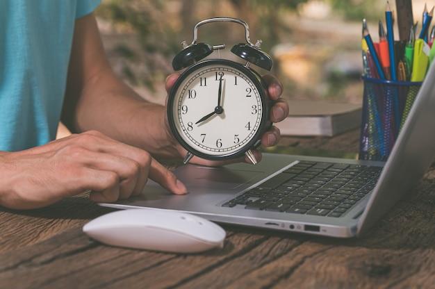 La mano che tiene l'orologio è alla scrivania.