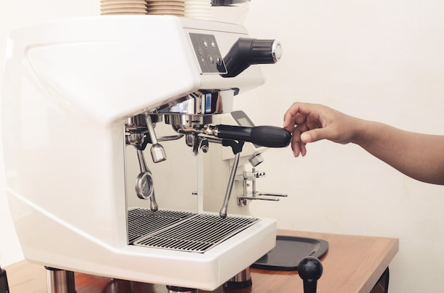 Mano che tiene la macchina da caffè nella caffetteria. concetto di caffetteria
