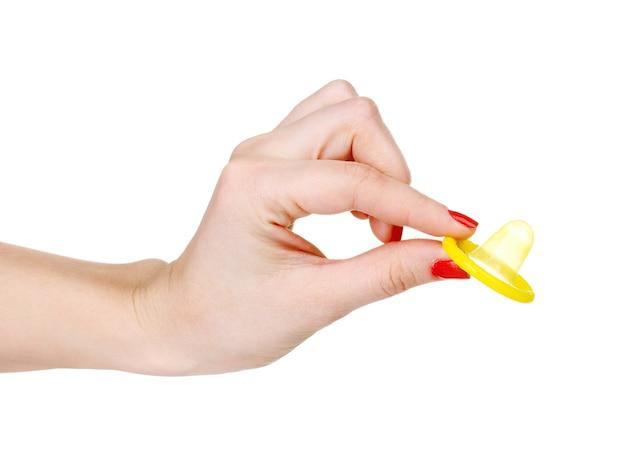 Mano che tiene un preservativo su bianco