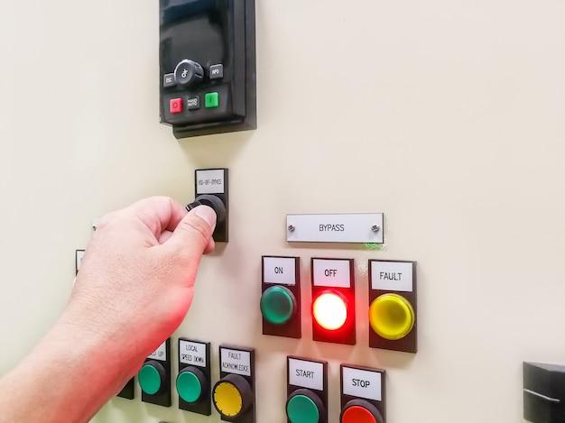 Mano che tiene il pannello di controllo dell'impianto industriale e premendo o ruotando il pulsante nel selettore elettrico, nel quadro elettrico del centro di controllo del motore dell'interruttore a pulsante