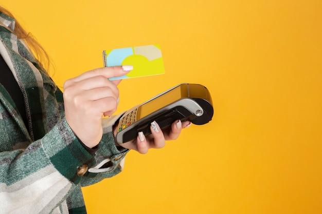 Mano che tiene la carta di credito e il dataphone