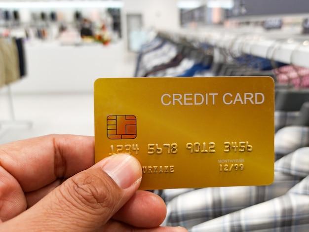 Mano che tiene la carta di credito nel grande magazzino sullo sfondo del negozio di vestiti