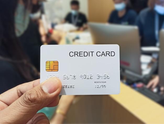 Mano che tiene la carta di credito nel grande magazzino sopra il negozio
