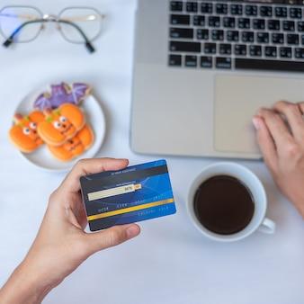 Mano che tiene la carta di credito per lo shopping online sul laptop durante il consumo di biscotti e caffè di halloween. buon halloween, ciao ottobre, autunno autunno, festivo, festa e concetto di vacanza