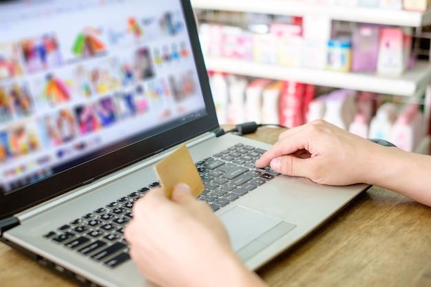 Mano che tiene la carta di credito e utilizza il pagamento del laptop per lo shopping online