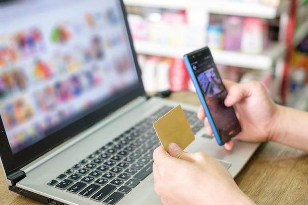Mano che tiene la carta di credito e utilizza il laptop con lo smartphone per lo shopping di pagamento online