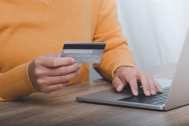 Mano che tiene la carta di credito e utilizzo del computer portatile.