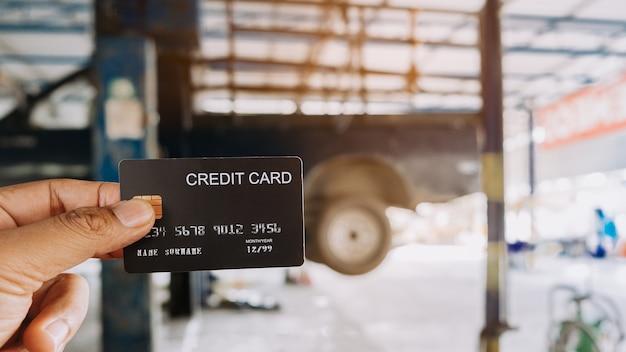 Mano che tiene una carte di credito all'officina riparazioni auto